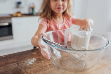 Selective focus of kid mixing flour in measuring jug near whisk in glass bowl while cooking on kitchen table stock vector