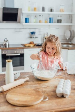Selective focus of child mixing flour in glass bowl with whisk near bottle of milk, rolling pin and eggs on kitchen table stock vector
