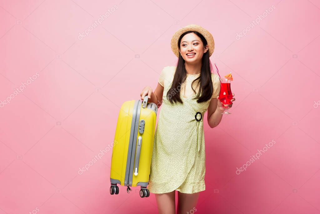 Cheerful asian girl in straw hat holding cocktail and yellow baggage on pink stock vector