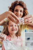 selektivní zaměření matky přidání kuřecího vejce do skleněné mísy v blízkosti dcery