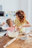 szelektív fókusz anya gyúrás tészta, miközben néz lánya a konyhában