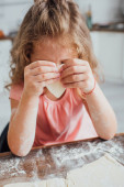 Photo little girl holding heart-shaped piece of dough while preparing cookies in kitchen