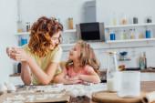 mladá matka s dcerou dívá na sebe při přípravě sušenek v kuchyni