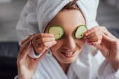 vágott kilátás a gyermek alkalmazása friss uborka szeletek szemén anya, szelektív fókusz