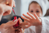 abgeschnittene Ansicht einer Frau, die roten Lack auf die Fingernägel ihrer Tochter aufträgt, selektiver Fokus