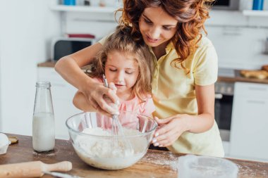 Selective focus of mom kneading dough in glass bow near daughter and bottle of milk stock vector