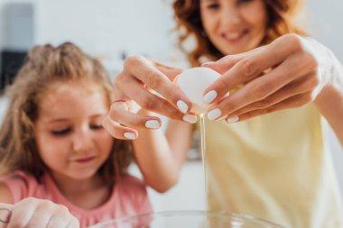 Annenin, kızının yanındaki cam kaseye tavuk yumurtası koyduğu seçici odak noktası.