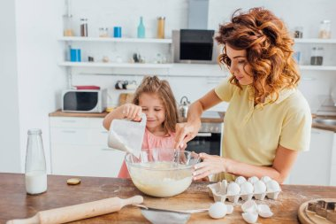 Daughter adding flour in glass bowl while mother kneading dough stock vector