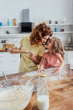 selective focus of mother holding rolling pin and daughter scattering flour while standing face to face at kitchen table