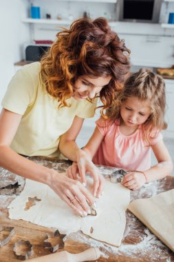 High angle view of curly mom and blonde daughter cutting out cookies from rolled dough stock vector