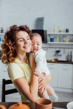 Selective focus of young mother with closed eyes holding infant boy in kitchen stock vector