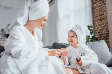 Selective focus of young woman making manicure to child while sitting together in white bathrobes and towels on heads stock vector