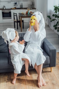 high angle view of woman putting on face mask while sitting with daughter in bathrobes and towels on heads