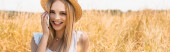 panoramic shot of young blonde woman in straw hat looking at camera while talking on smartphone in field