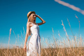 selective focus of stylish young woman in white dress touching straw hat and looking away against blue sky