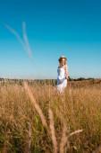 selektivní zaměření stylové ženy v bílých šatech a slaměný klobouk stojící na poli proti modré obloze