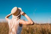back view of blonde woman in summer outfit touching straw hat in grassy meadow against blue sky, selective focus
