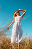 selective focus of woman in white dress touching straw hat while standing with outstretched hand against blue sky