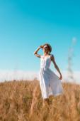 selektiver Fokus der stilvollen Frau, die weißes Kleid und Strohhut berührt, während sie mit geschlossenen Augen im Feld steht