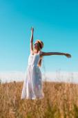 selektivní zaměření smyslné ženy v bílých šatech stojící s nataženýma rukama a zavřenýma očima na travnatém poli