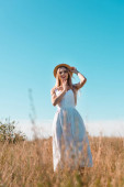 selective focus of blonde woman in white dress touching straw hat and holding hand near face while standing in field