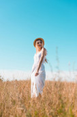 selective focus of blonde woman in white dress and straw hat standing in field against blue sky and looking away