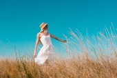 Selektiver Fokus der blonden Frau in weißem Kleid und Strohhut, die mir Geste auf der Wiese zeigt