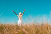 pohled na ženu v slaměném klobouku a bílých šatech stojící se zdviženýma rukama na travnaté louce, selektivní zaměření