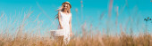 selective focus of blonde woman in white dress and straw hat standing on wind in field, horizontal concept