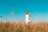 selective focus of stylish woman in white dress and straw hat looking at camera in grassy meadow against blue sky