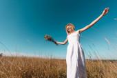 alacsony szög kilátás elegáns nő fehér ruhában gazdaság csokor vadvirágok, miközben áll kinyújtott kézzel