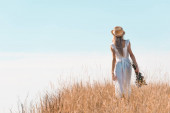 back view of woman in white dress and straw hat holding wildflowers while standing on grassy hill