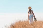 zpět pohled na ženu v bílých šatech a slaměný klobouk drží divoké květiny, zatímco stojí na travnatém kopci