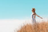 Blondine mit Strohhut und weißem Kleid steht mit ausgestreckten Händen auf einem Hügel vor blauem Himmel