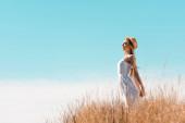 Seitenansicht einer jungen Frau in weißem Kleid und Strohhut, die mit geschlossenen Augen auf einem grasbewachsenen Hügel steht