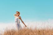 selektivní zaměření smyslné ženy v bílých šatech dotýkající se slaměného klobouku, zatímco stojí s nataženýma rukama proti modré obloze