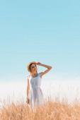 junge Frau in weißem Kleid steht auf einem grasbewachsenen Hügel, berührt Strohhut und blickt gegen den blauen Himmel