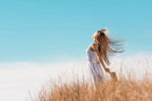 selective focus of blonde woman in white dress holding straw hat while standing with raised hand on grassy hill