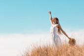 selektivní zaměření blondýny ženy v bílých šatech drží slaměný klobouk, zatímco stojí se zvednutou rukou na travnatém kopci