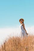 selektivní zaměření mladé ženy v slamníku dotýkající se bílých šatů při stání na travnatém kopci