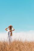 selektiver Fokus einer stilvollen Frau in weißem Kleid, die Strohhut berührt, während sie mit erhobenem Kopf gegen bule Himmel steht