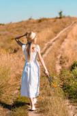 zpět pohled na mladou ženu v bílých šatech dotýkající se slaměný klobouk při chůzi na silnici v poli s kyticí divokých květin