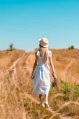 zpět pohled na mladou ženu v bílých šatech a slamák kráčející v poli s kyticí divokých květin