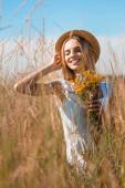 selektiver Fokus einer jungen sinnlichen Frau, die Strohhut berührt, während sie Wildblumen im Grasfeld hält
