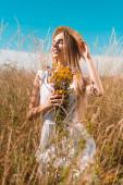 selektivní zaměření blondýny žena v bílých šatech a slamák klobouk drží kytice divokých květin při dotyku slaměný klobouk