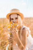 selektivní zaměření blondýny v slaměném klobouku při pohledu na kameru při držení divokých květin na travnaté louce