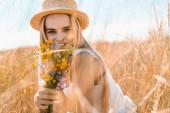 Selektiver Fokus einer jungen Frau mit Strohhut, die Wildblumen in der Hand hält und auf der Wiese in die Kamera blickt
