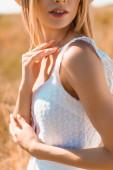 oříznutý pohled na smyslnou mladou ženu v letním oblečení dotýkající se krku na slunci