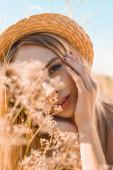 portrét zasněné blondýny v slamáku dotýkající se obličeje a při pohledu na kameru v blízkosti divokých květin