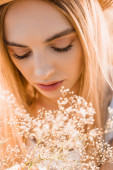portrét zamyšlené blondýny v blízkosti divokých květin, selektivní zaměření